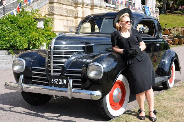 Lady in 1940s clothing leaning on a vintage car