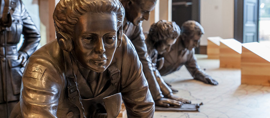 Bronze style model of a women leaning over a map of Britain in the Museum's recreation of a Filter Room