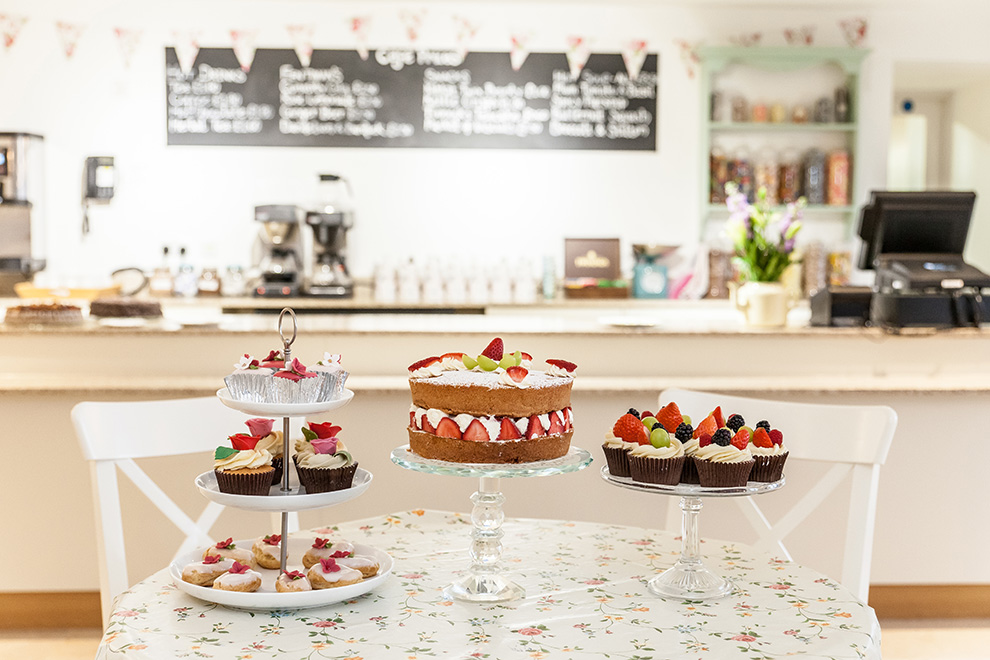 Victoria Sponge cake and fruit-topped cupcakes on display in the Museum's Cafe.
